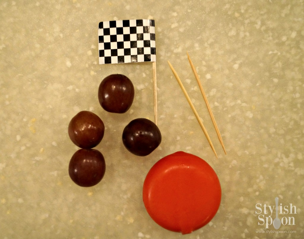 For each cheese race car you will need 1 Babybel cheese round, 4 grapes that are all about the same size, two plain toothpicks and 1 checked flag toothpick (see note about where to buy the pre-made checkered flag picks or how to make them with the free printable template).