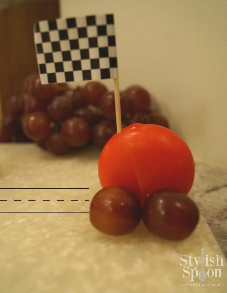 """Step 6 - Place the checkered flag picks in each """"car"""" towards one side. To easily transport these cheese race cars, wrap them individually in plastic wrap."""
