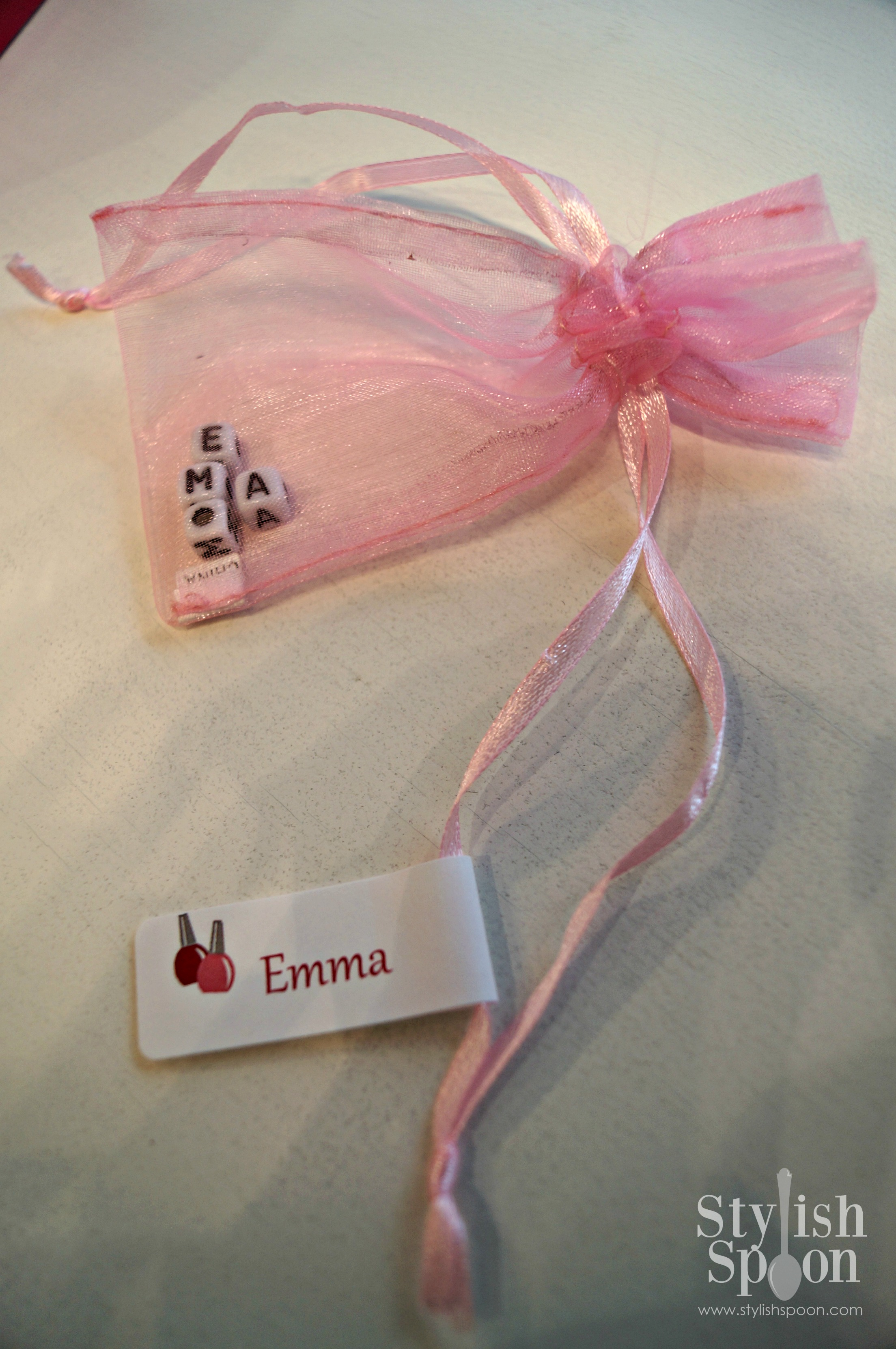 Name beads in pink organza jewelry bags.